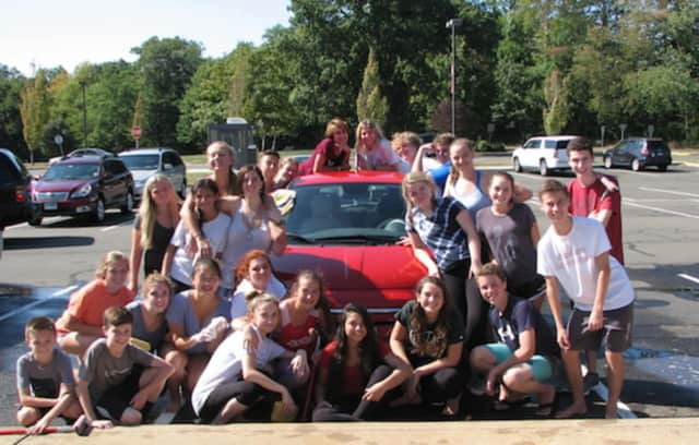 The New Canaan High School Theatre Department celebrates a successful car wash fundraiser.