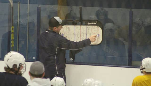 Coach Anthony Tabbacchino goes over plays with the Indian Hills hockey team.