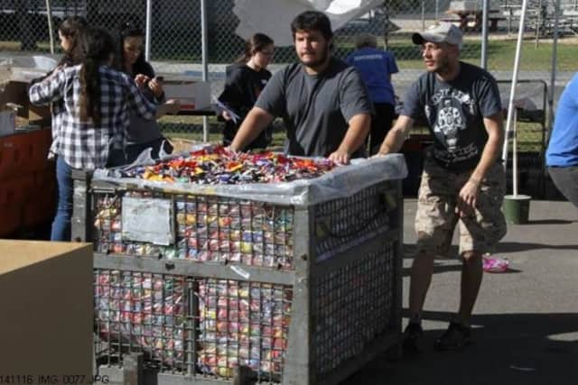 Volunteers help sort through the hundreds of pounds of candy donated to the troops.
