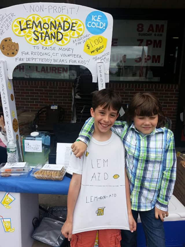 Vladimir Schwindeman-Romano is shown with a friend at True Value of Bethel where he runs a lemonade stand to raise money for teddy bears. The stuffed toys are then donated to fire departments for kids on ambulances.